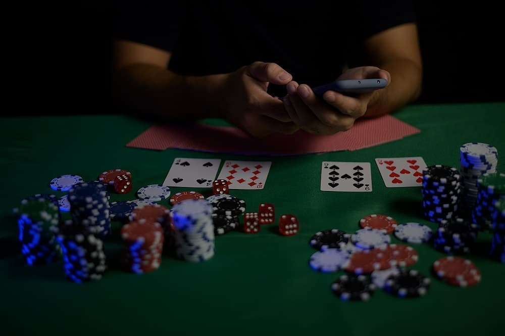 Casino worker dealing from the deck of cards and betting on his mobile phone.